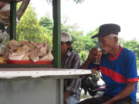 An old man drinking tea at a warung